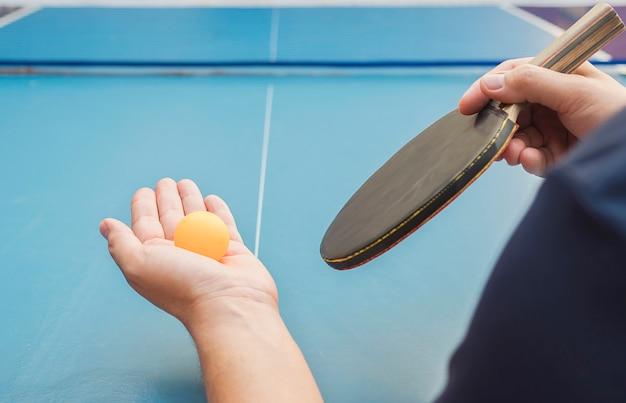 Um homem joga tênis de mesa pronto para servir
