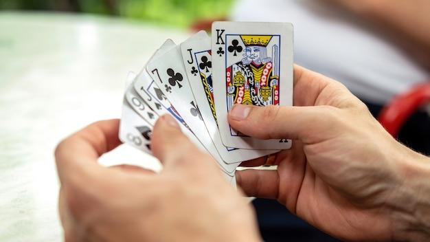 Um homem jogando cartas com outras pessoas segurando um baralho