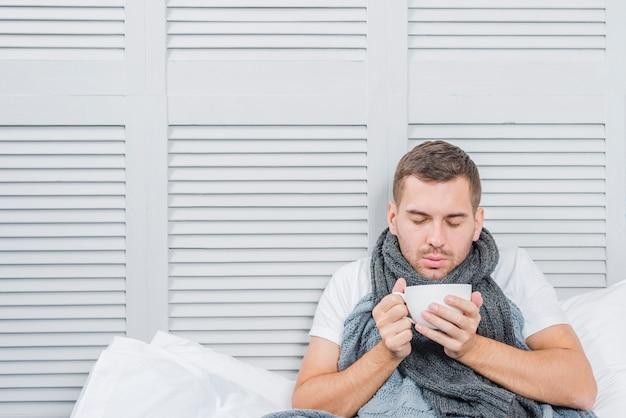 Um, homem jovem, desgastar, cinzento, echarpe, ao redor, dela, pescoço, segurando, branca, xícara café