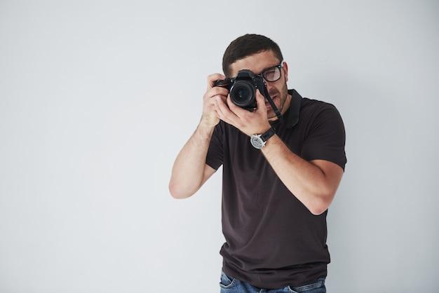 Um homem jovem hippie em oculares segura uma câmera dslr nas mãos de pé contra uma parede branca