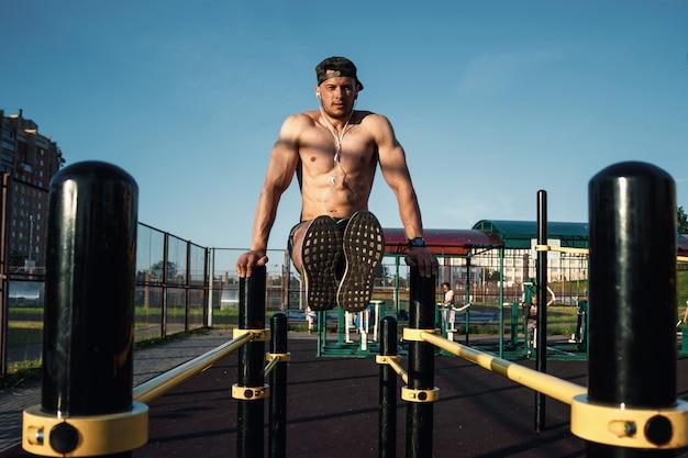 Um, homem jovem, levanta, seu, pernas, ligado, um, esportes, chão, um, atleta, treinamento ao ar livre, cidade