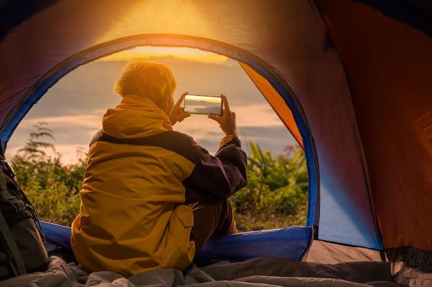 Um, homem jovem, sentando, em, a, barraca, com, levando, foto, com, um, telefone móvel