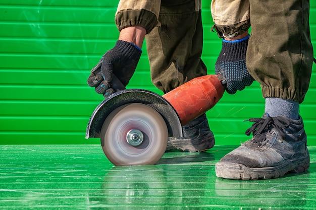 Um, homem jovem, soldador, em, um, trabalhando, global, e, luvas trabalho, mói, um, metal, objeto, com, um, rebarbate