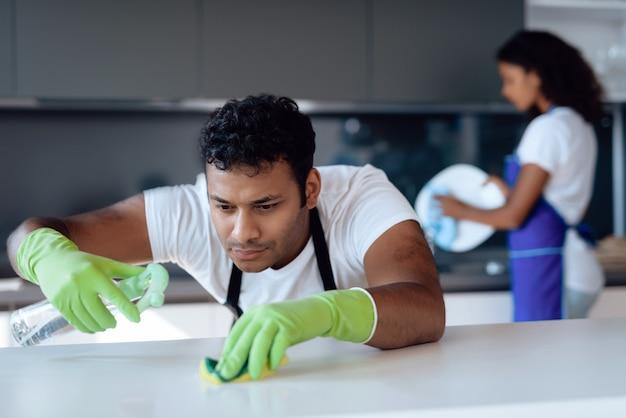 Um homem lava a bancada com detergente