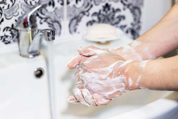 Um homem lava as mãos com sabão no banheiro. higiene pessoal. desinfecção e precauções durante uma pandemia