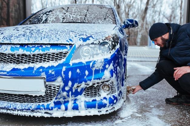Um homem lava discos de titânio com uma toalha. lavagem de carros self-service
