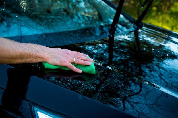 Um homem lava o carro com uma esponja e derrama água nele com uma mangueira.