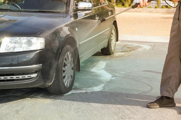 Um homem lava um carro em uma lavagem manual.
