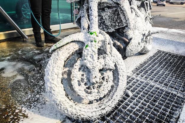 Um homem lava uma motocicleta. a espuma de lavagem especial remove a sujeira.
