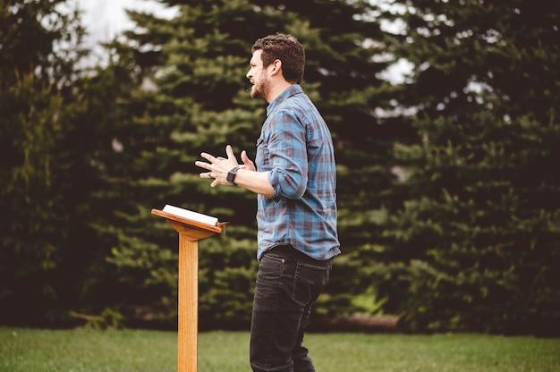 Um homem lendo a bíblia em pé perto do pódio