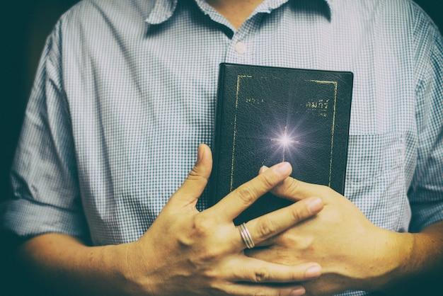Um homem lendo a bíblia sagrada.