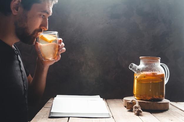 Um homem lendo um livro com chá de frutas cítricas. educação, bebida saudável, treinamento.