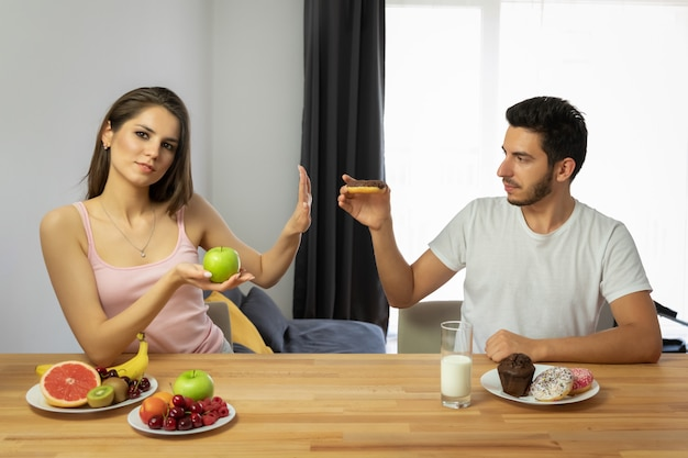 Um homem leva um estilo de vida errado, ele come alimentos doces e com altas calorias no café da manhã.