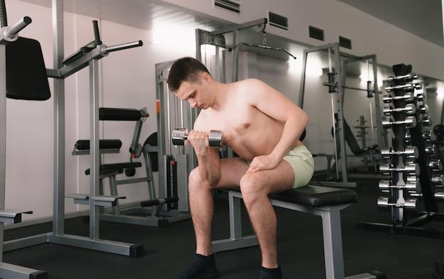 Um homem levanta halteres na sala de ginástica. um homem pratica esportes em um centro esportivo. uma pessoa se preocupa com sua saúde. torso nu