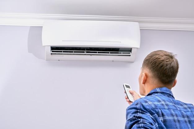 Um homem liga o ar condicionado com o controle remoto em casa
