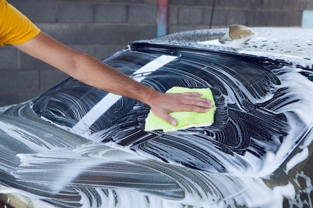 Um homem limpa a espuma do carro com um pano. lava-jato