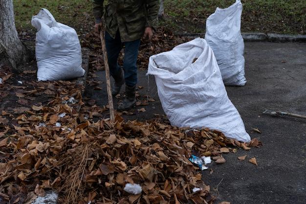 Um homem limpa e varre um quintal