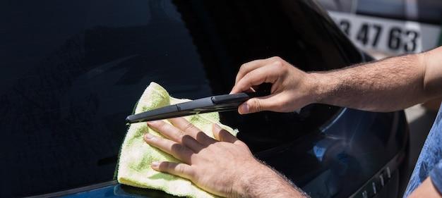 Um homem limpa um carro molhado com um pano