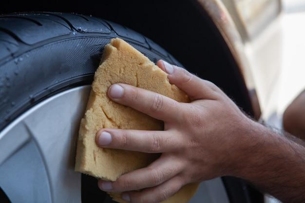 Um homem limpa uma roda com uma esponja