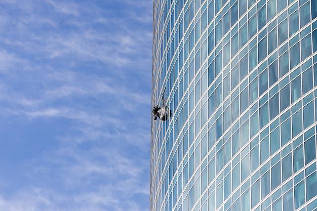 Um homem limpando janelas em um prédio alto. alpinista industrial pendurado no varal e lava janelas, edifício moderno com fachada de vidro.