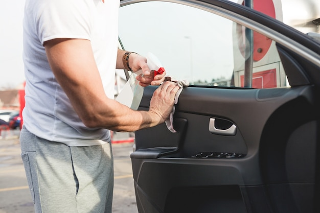 Um homem limpando o carro com pano de microfibra, conceito de detalhamento (ou manutenção) do carro. foco seletivo na mão do homem.