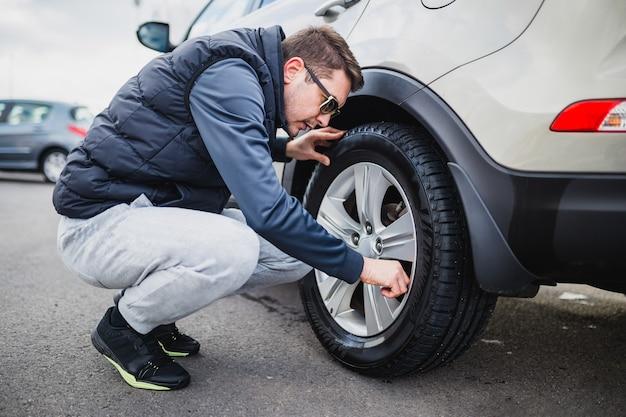 Um homem limpando o carro com pano de microfibra, conceito de detalhamento (ou manutenção) do carro.