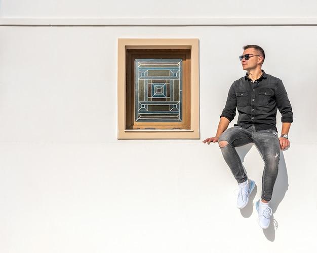 Um homem localizado em uma parede branca perto de uma janela colorida.