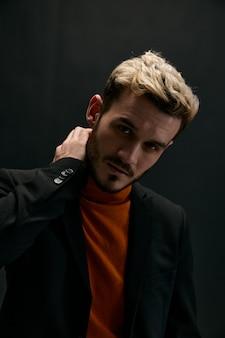 Um homem loiro com um suéter e uma jaqueta toca seu pescoço em um plano de fundo escuro