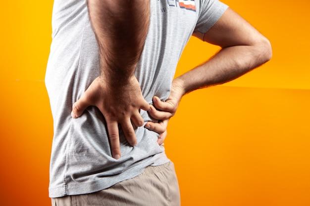 Um homem machuca os rins em um fundo laranja