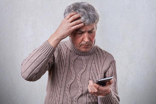 Um homem maduro com problemas, segurando a mão na cabeça cinza enquanto usa o smartphone lendo algumas notícias na internet