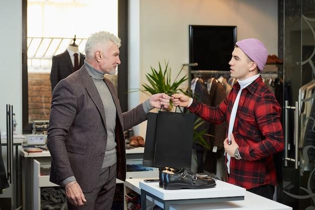 Um homem maduro de cabelos grisalhos e físico esportivo está levando sacolas de papel preto com as compras de um vendedor em uma loja de roupas. uma vendedora feliz está dando sacolas de papel para um cliente do sexo masculino.