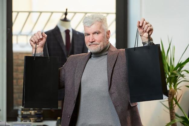 Um homem maduro e feliz com cabelos grisalhos e um físico esportivo está mostrando duas sacolas de papel preto com compras em uma loja de roupas. um cliente do sexo masculino com barba usa um terno de lã em uma boutique