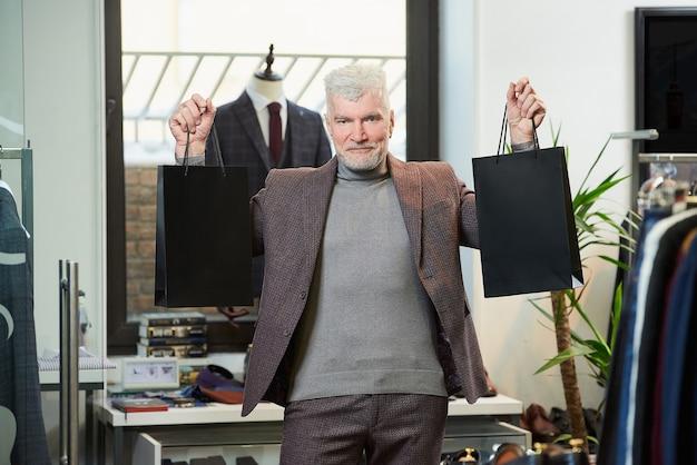 Um homem maduro e feliz com cabelos grisalhos e um físico esportivo está mostrando duas sacolas de papel preto com compras em uma loja de roupas. um cliente sorridente com barba usa um terno de lã em uma boutique