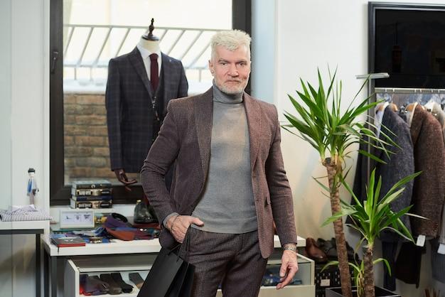 Um homem maduro e feliz com cabelos grisalhos e um físico esportivo está posando com suas compras em sacolas de papel preto em uma loja de roupas. um cliente do sexo masculino com barba usa um terno de lã em uma boutique