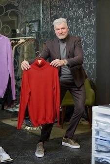 Um homem maduro e feliz com cabelos grisalhos está exibindo uma blusa de gola alta vermelha em uma loja de roupas. um cliente do sexo masculino com barba usa um terno de lã em uma boutique.