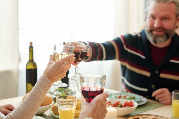Um homem maduro e sua filha brindando com taças de vinho durante os lanches servidos na mesa do jantar em família no dia de ação de graças
