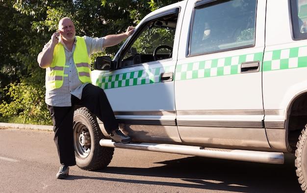 Um homem maduro, fazendo uma ligação ao lado de sua caminhonete