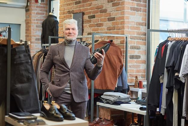 Um homem maduro, feliz, com cabelos grisalhos e um físico esportivo, posa segurando um sapato preto em uma loja de roupas. um cliente do sexo masculino com barba usa um terno de lã em uma boutique