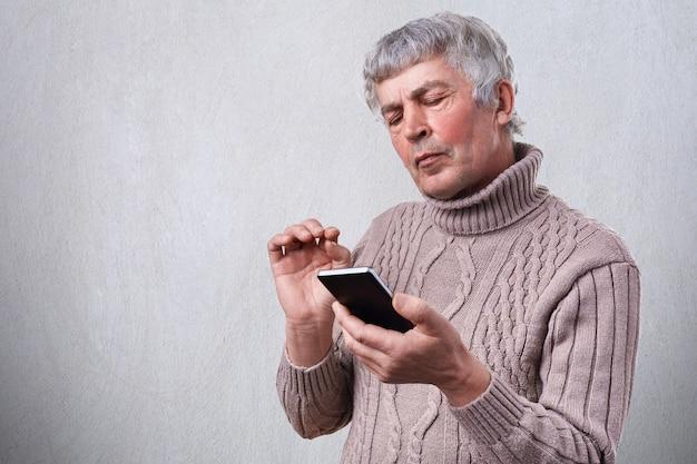Um homem maduro sério segurando o smartphone na mão, olhando atentamente para a tela. último homem lendo a mensagem de texto no telefone