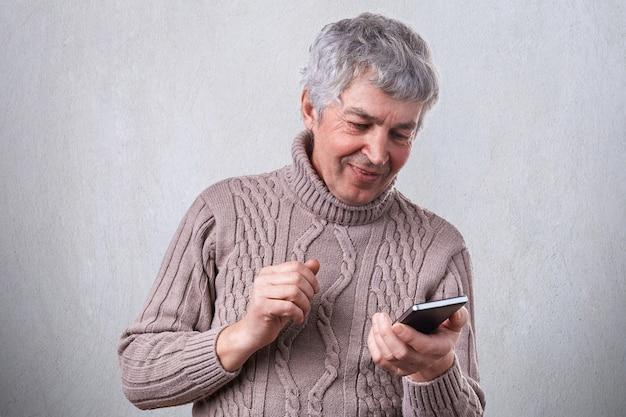 Um homem maduro sorridente feliz segurando seu smartphone nas mãos, sendo o prazer de receber a mensagem de seu filho