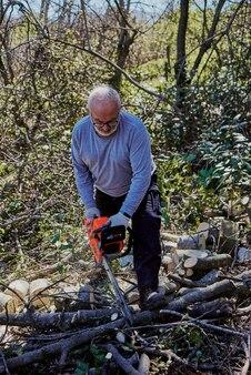 Um homem mais velho está cortando lenha com uma serra elétrica