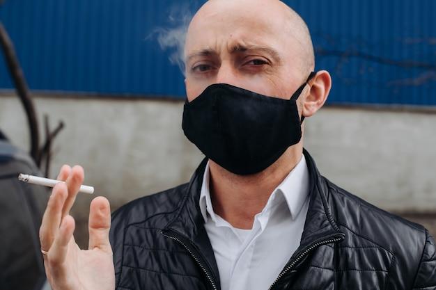 Um homem mascarado durante a pandemia de covid-19 fuma na rua. careca, negro