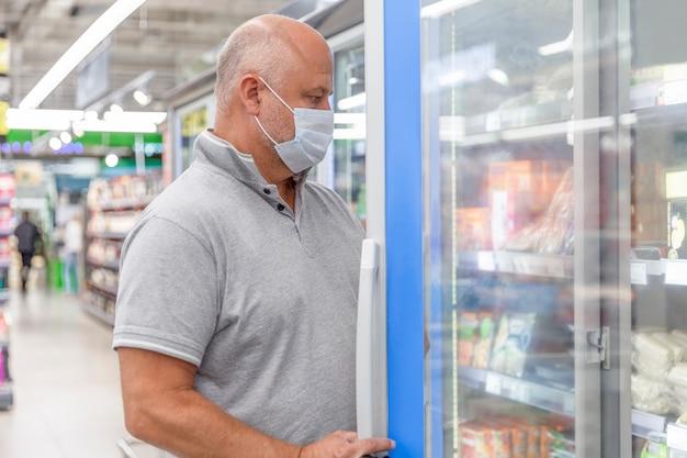 Um homem mascarado em um supermercado escolhe alimentos congelados de conveniência