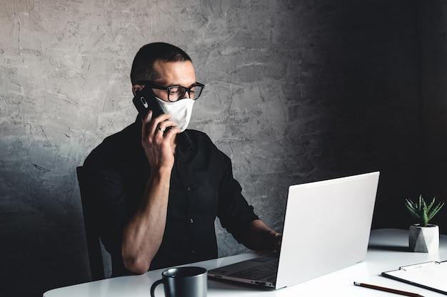 Um homem mascarado trabalha em um computador. pandemia, coronavírus, epidemia