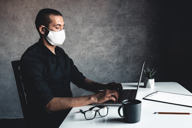 Um homem mascarado trabalha em um computador
