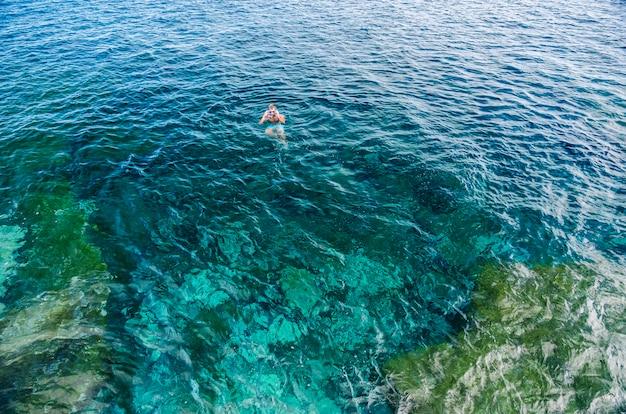 Um homem mergulha com óculos e tubo e toma banho no mar com a cor azul turquesa