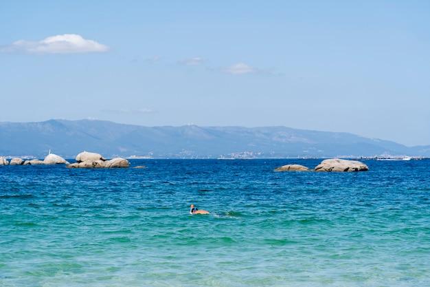 Um homem mergulha em uma praia paradisíaca