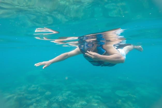 Um homem mergulhando de snorkel em um recife de coral em uma praia