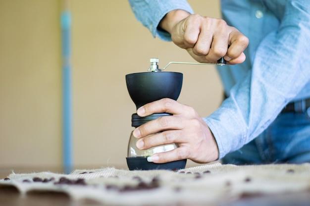 Um homem mói os grãos de café com uma batedeira.