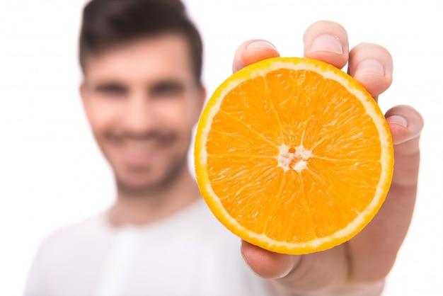 Um homem mostra uma laranja na mão.